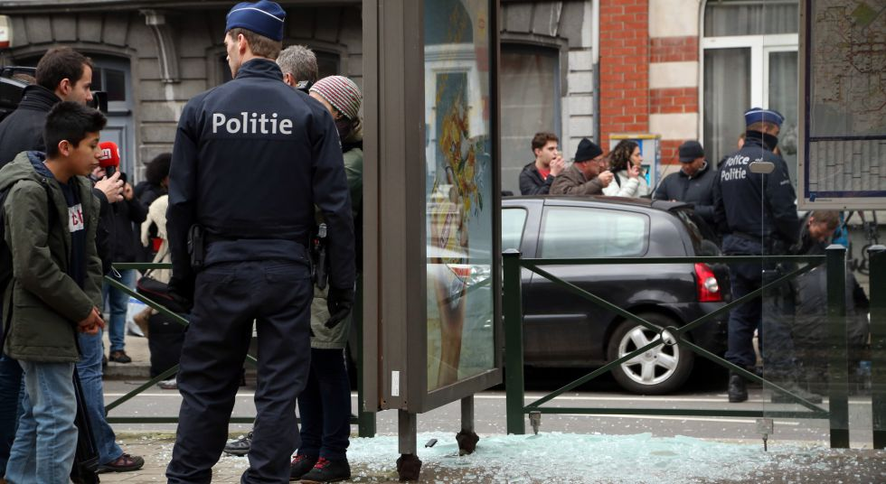 Un policía vigila al lado de un cristal roto por una explosión controlada, durante una redada en el barrio bruselense de Schaerbeek.