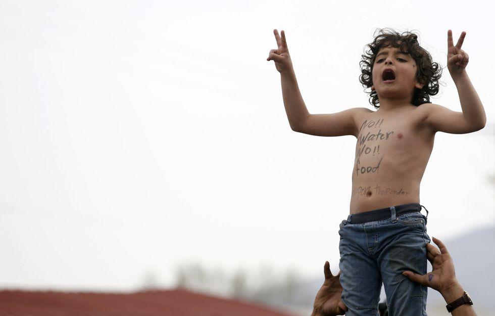 """Un niño protesta en la frontera entre Grecia y Macedonia por la falta de agua y alimentos. """"Ni agua ni comida"""", dice el eslogan pintado en el pecho."""