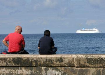 Dos hombres observan un crucero que cruza frente al malecón en La Habana.
