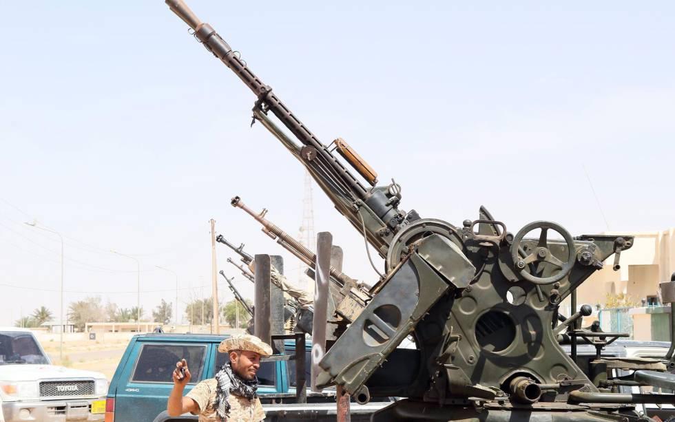 Un miembro de las milicias libias leales al Gobierno de Unidad, delante de varias armas situadas en el puesto de control de Abú Grain, al este de Misrata, el 18 de mayo.rn