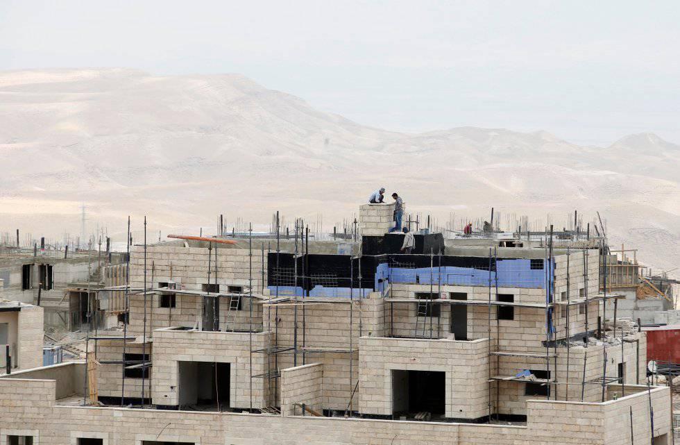 Obreros trabajan en la construcción de un edificio en el asentamiento judío cisjordano de Maale Adumim en mayo de 2014.