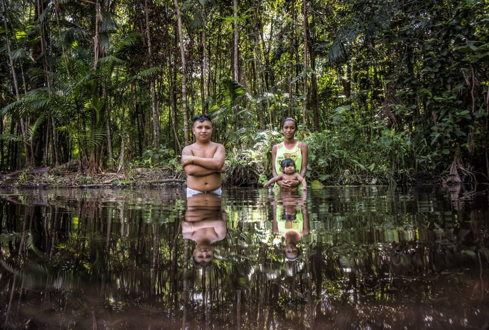 Um casal com seu bebê no rio, a única fonte de água.