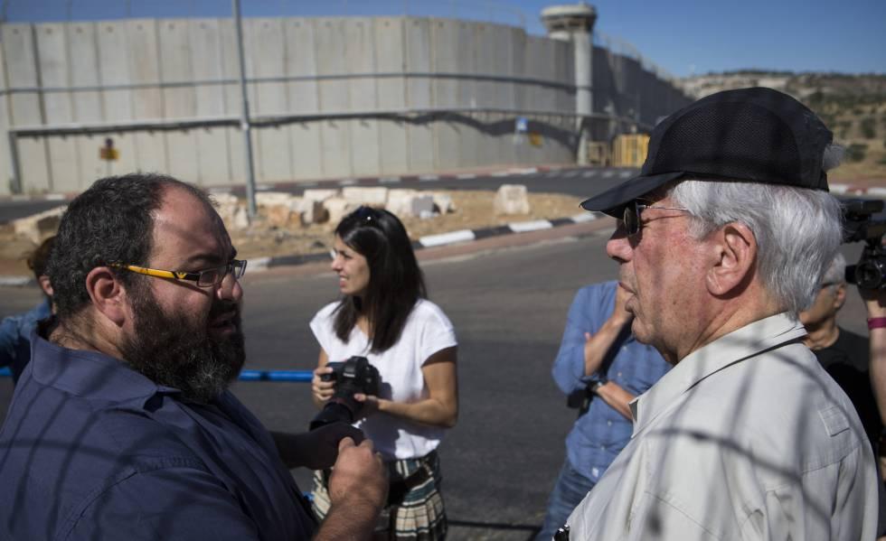 Vargas Llosa (d), em conjunto com Yehuda Shaul (Quebrando o Silêncio), na saída de Jerusalém, com o fundo da parede divisória