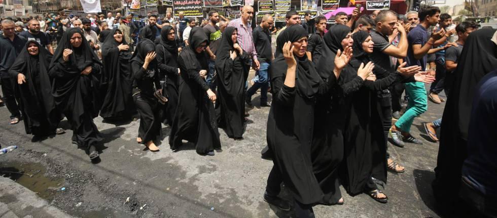Un cortejo fúnebre pasa por el lugar del atentado del domingo en Bagdad.
