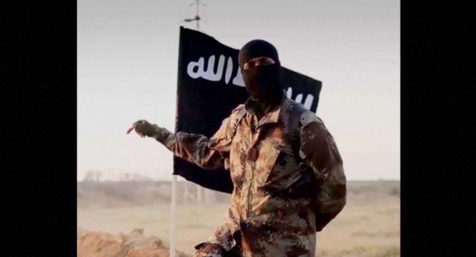 A masked man with an ISIS flag in the background.