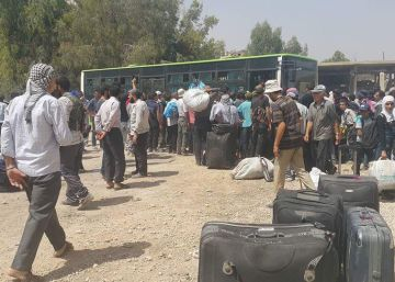 Civiles en Dayara (Siria) esperan a los autobuses que los llevan a la localidad de Qudsiya.