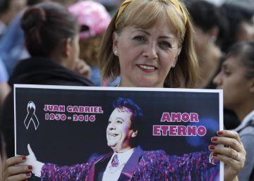 Una mujer sostiene un póster de Juan Gabriel en México.