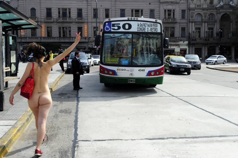 Una de las integrantes de UrbaNudismo simula parar un bus.