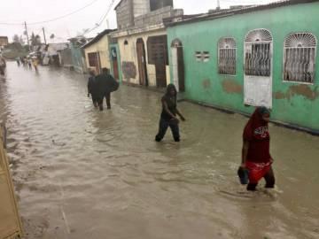 Un grupo de personas caminan por las calles inundadas de Puerto Príncipe.