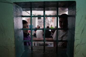 Dos internos conversan desde el interior de un pabellón.