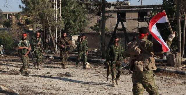 Soldados sirios se adentran, este domingo, en el barrio rebelde de Awijah (Alepo).