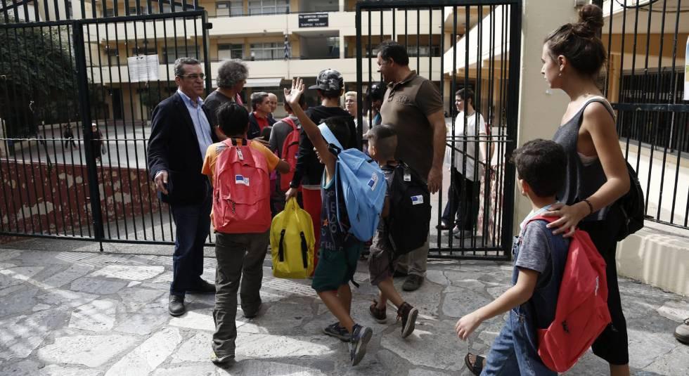 Niños refugiados a la entrada de un colegio en Atenas.