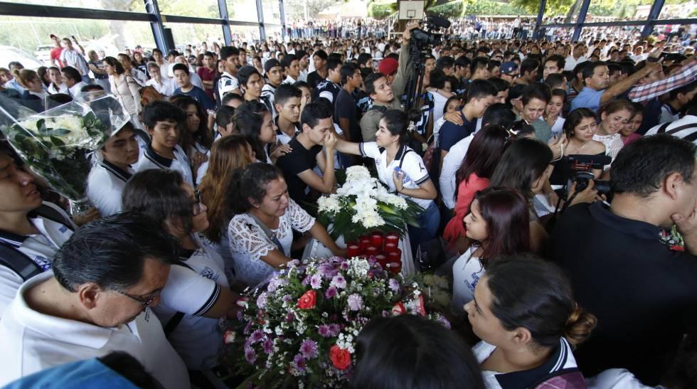 Amigos y compañeros de las víctimas en su funeral.
