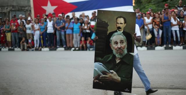 Un hombre con un retrato de Martí y Castro en Santiago.