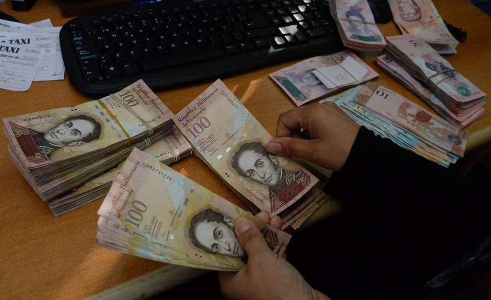 Una mujer cuenta billetes de 100 bolívares en Caracas.