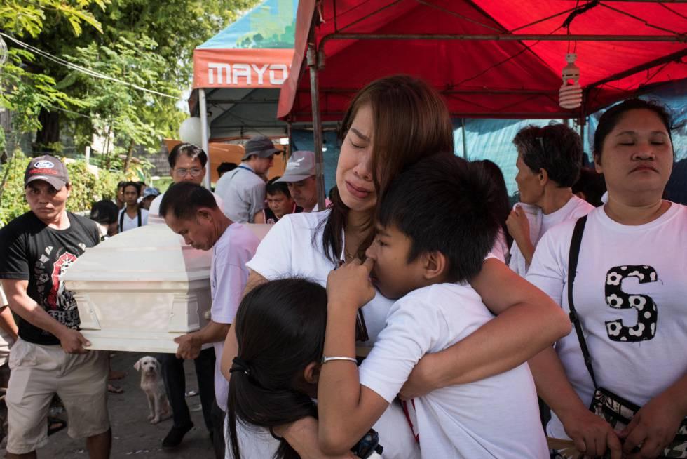 La esposa y los hijos de Alex Hongco lloran mientras sus parientes llevan el ataúd con su cuerto. Hongco y tres hombres más fueron asesinados cuando la policía irrumpió en una casa de Manila en una redada antidroga en diciembre pasado.