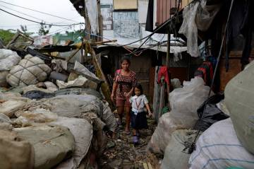 Weng Ruda, de 36 años y madre de tres niños, lleva a su hija a la escuela en el área depauperada de Quezón.