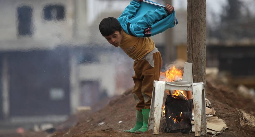 Un niño se calienta, este jueves, con un fuego en la ciudad rebelde de al-Rai.
