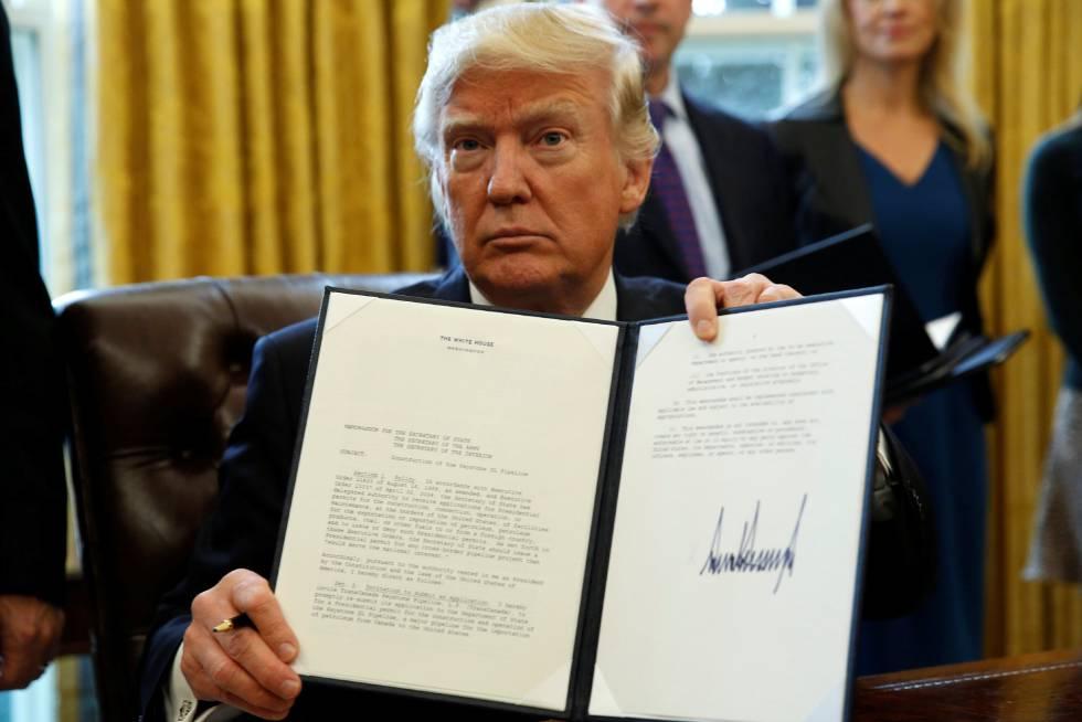 Donald Trump muestra su firma sobre una orden ejecutiva.
