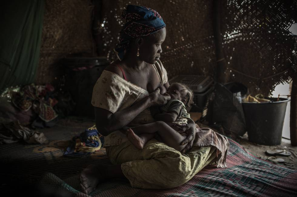 Una madre alimenta a su hijo con desnutrición en un campo de refugiados.