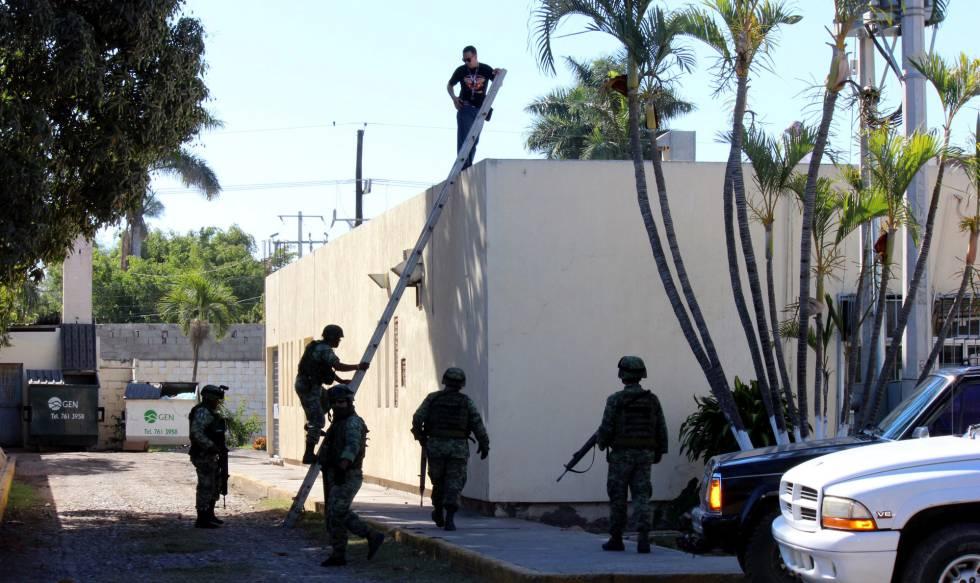 Un grupo de soldados revisan el tejado donde fue hallado el cuerpo presuntamente lanzado desde una avioneta.