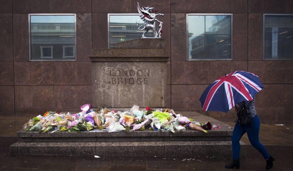 Una mujer pasa delante de varios ramos de flores dejados en memoria de las víctimas del atentado del sábado en el Puente de Londres.