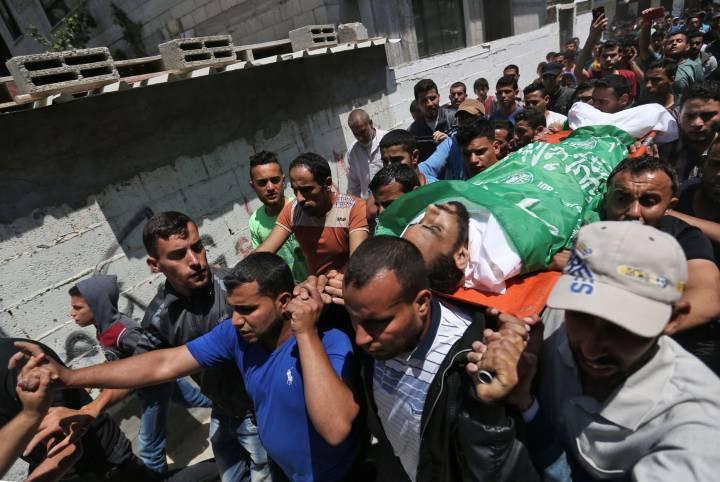 Varios palestinos llevan el cuerpo de un hombre de 27 años, muerto ayer durante las protestas, durante su funeral en Nusseirat.