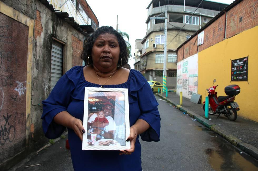 Denise de Moraes mostra uma foto de seu filho assassinado pela polícia.