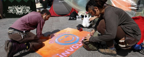 Dos 'acampados' en la Puerta del Sol preparan uno de los carteles.