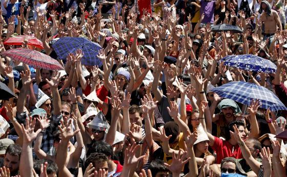 Los acampados de Sol levantan sus manos para votar en la asamblea.