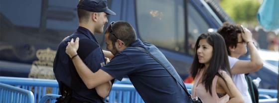 Una de las personas que han acudido a Sol se abraza a uno de los policías allí desplegado.