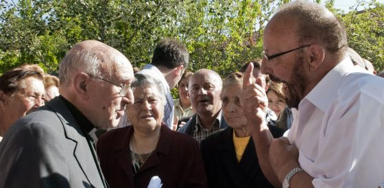 El vicario, a la izquierda, conversa con los vecinos de Piñor