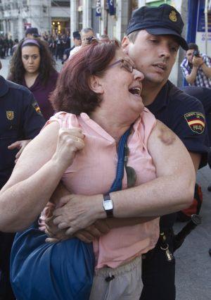La policía desaloja de Sol a una participante en la protesta.