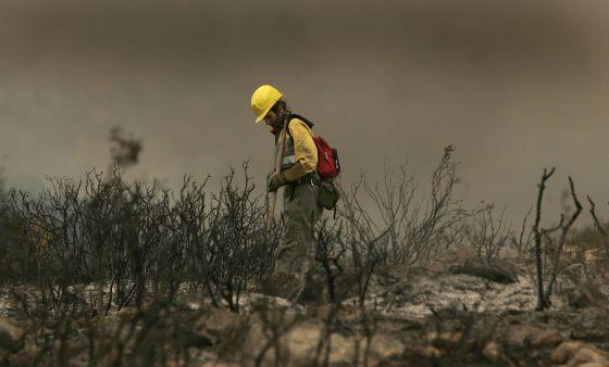 Un bombero apaga los rescoldos en Les Useres (Castellón)