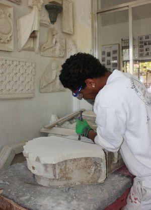 Un inmigrante en un taller de escultura en piedra.