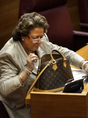 Rita Barberá busca algo en su bolso que lleva estampada la marca Louis Vuitton en un pleno de las Cortes.