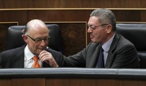 El ministro de Justicia, Alberto Ruiz-Gallardón, felicita al ministro de Hacienda, Cristóbal Montoro, tras su intervención en el Congreso.