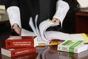 Un juez hojea varios libros de leyes.