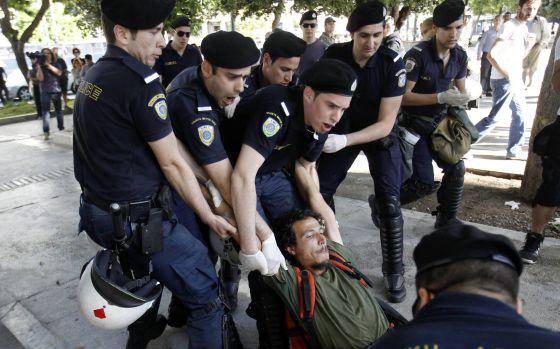 La policía detiene a uno de los indignados en la plaza Syntagma de Atenas.