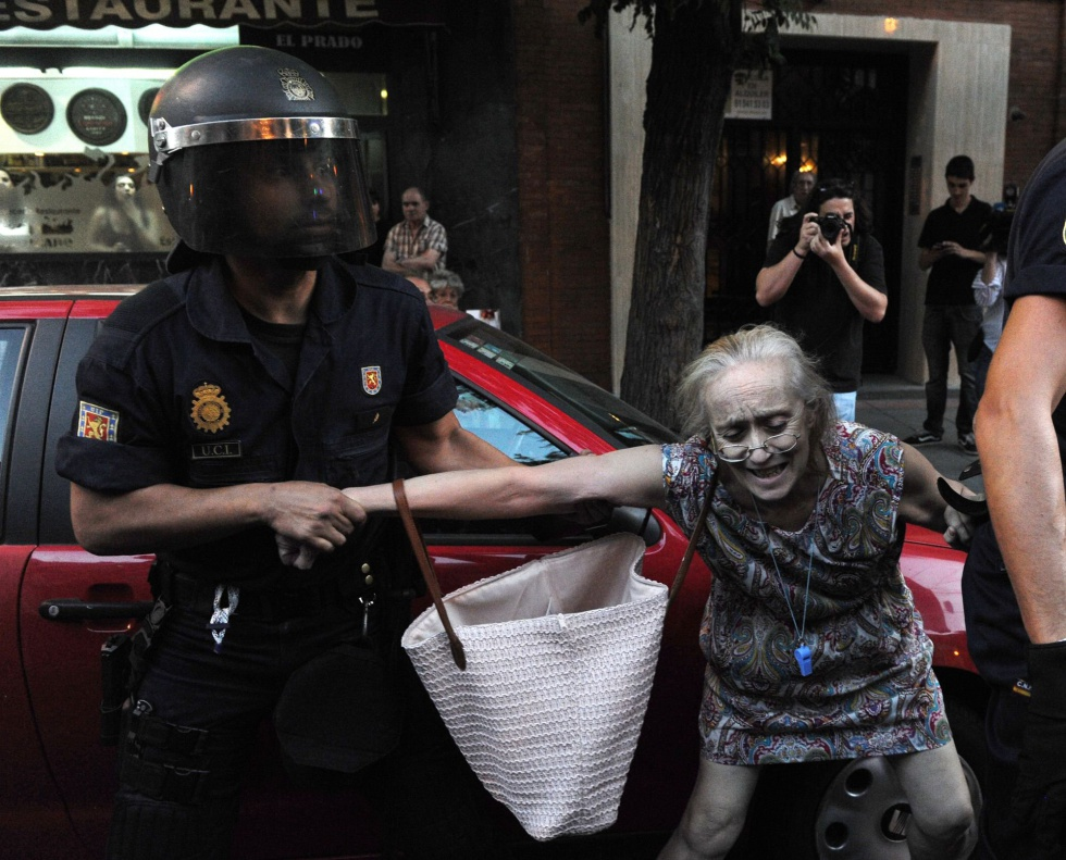Un agente antidisturbios agarra del brazo a una mujer en Madrid durante las protestas contra los recortes.