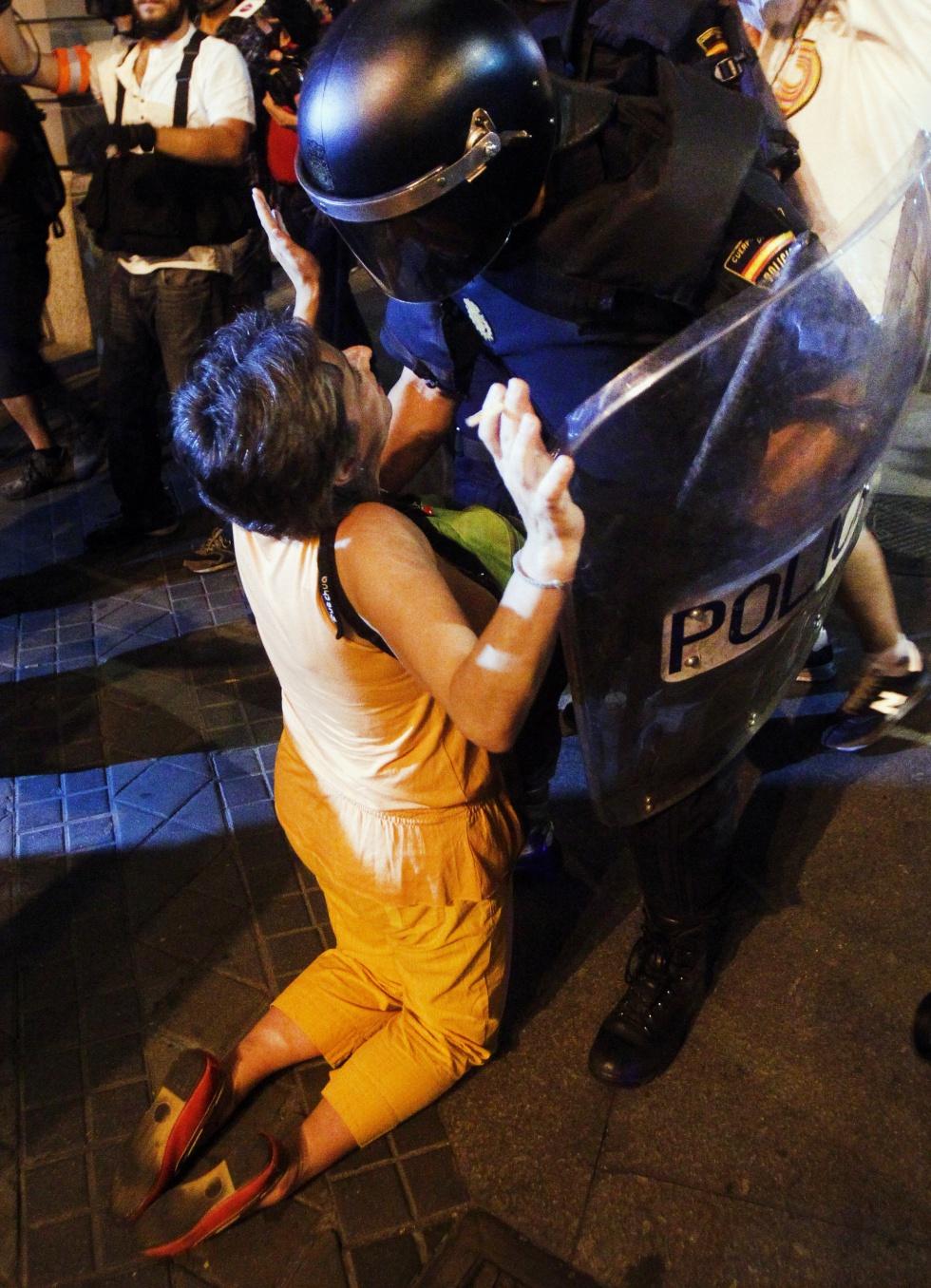 Una manifestante arrodillada ante un policía antidisturbios por la noche en Madrid.