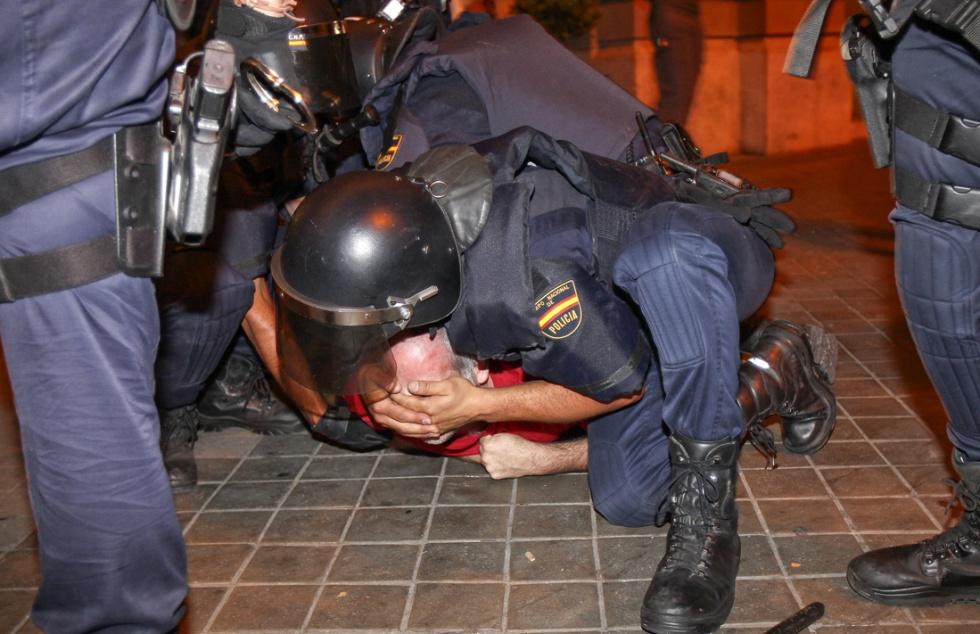 Varios policías reducen a un manifestante.