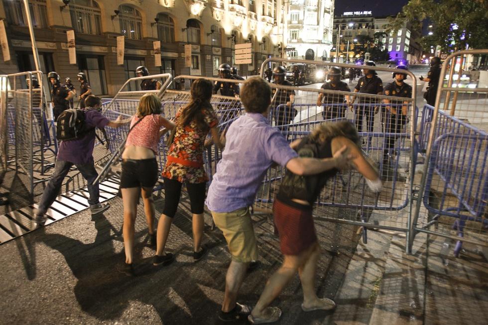 Un grupo de manifestantes trata de derribar una barrera de vallas colocada por la policía en las inmediaciones del Congreso de los Diputados.