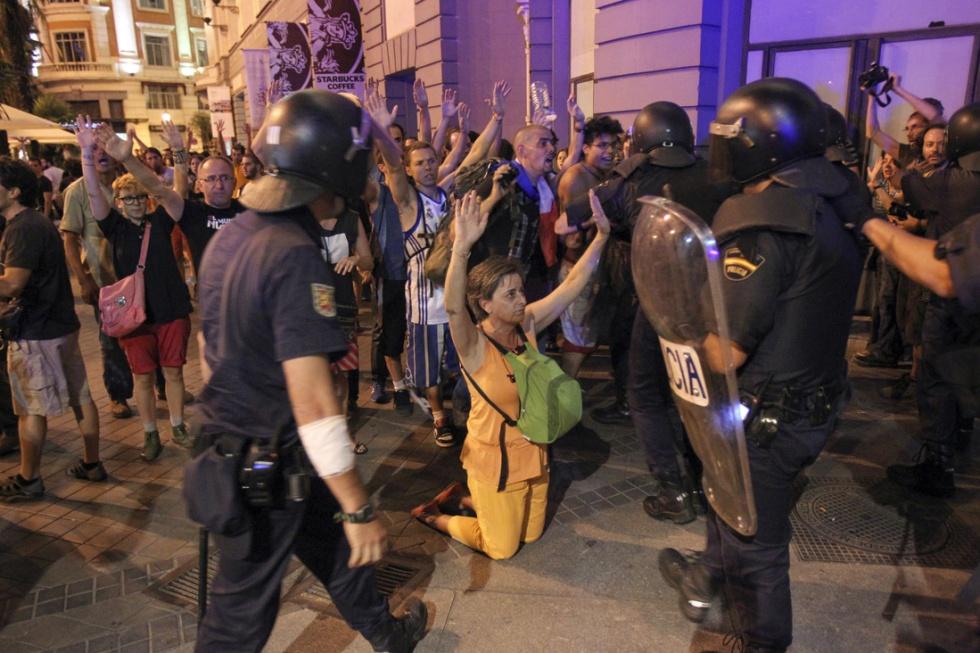 Una mujer protesta arrodillada ante los agentes de policía en el centro de Madrid.
