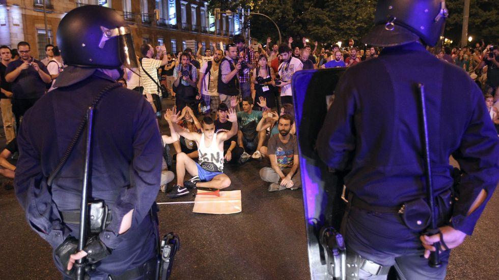 Participantes en las protestas de Madrid ocupan una calle ante un cordón policial tras choques entre agentes y manifestantes.