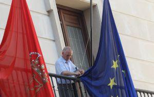 Un empleado municipal coloca a media asta las banderas del balcón del ayuntamiento.