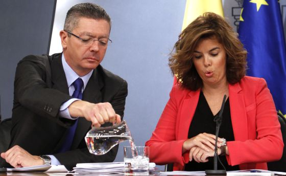 El ministro de Justicia sirve agua a Sáenz de Santamaría.