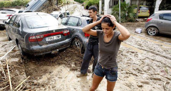 Dos vecinos de Vera (Almería) caminan entre lodo junto a varios vehículos arrastrados en las inundaciones.
