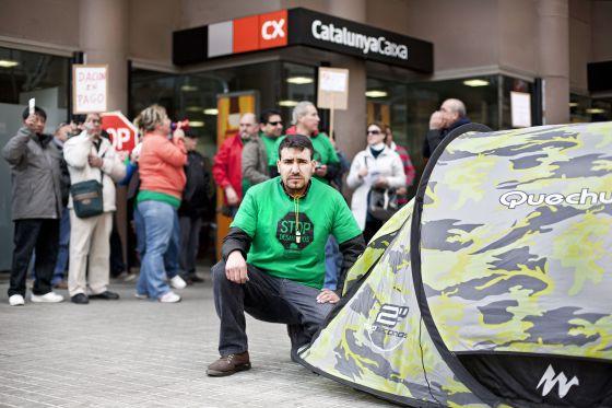 César Guerrero, un vecino del barrio de La Florida de L´Hospitalet de Llobregat, Barcelona, mantiene una acampada ante las puertas de una oficina de Catalunya Caixa.