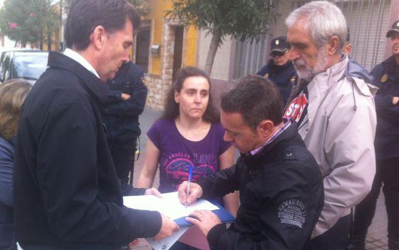 José Manuel Mengíbar, firma en presencia de su mujer, Lourdes Castro, los papeles del deshaucio de su casa.